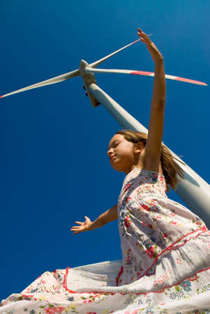 girl playing in the wind under a turbine photo