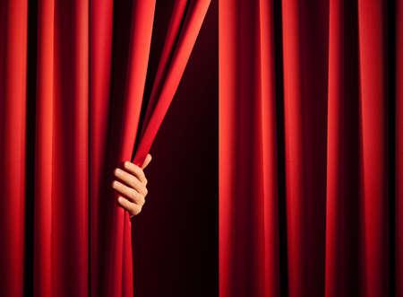 curtain theater: lado masculino en el acto de revelar la escena desplazando la cortina roja Foto de archivo