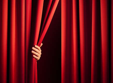 curtain theatre: male hand in the act of disclose the scene shifting the red curtain