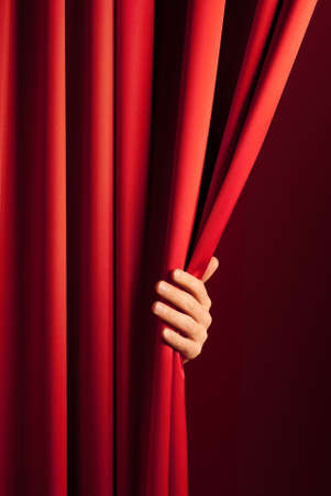 curtain theatre: male hand disclose the scene shifting the red curtain