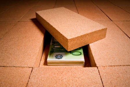 personal savings under a brick in the floor Stock Photo
