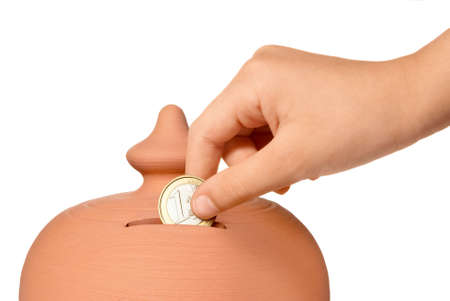 economize: young hand introducing one euro coin in the slot of a moneybox