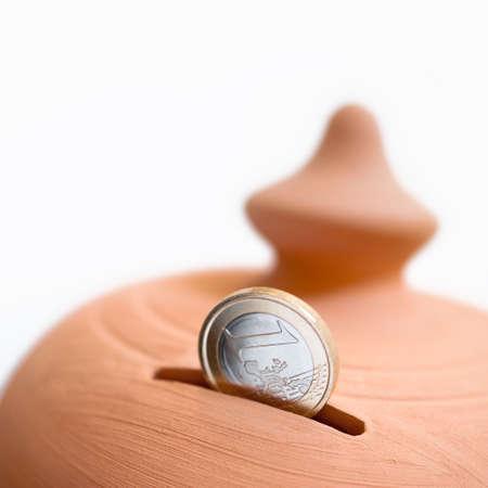 Ein-Euro-Münze in den Schlitz einer Sparbüchse