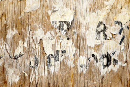 snatched: fragments of torn poster glued on wooden panel Stock Photo