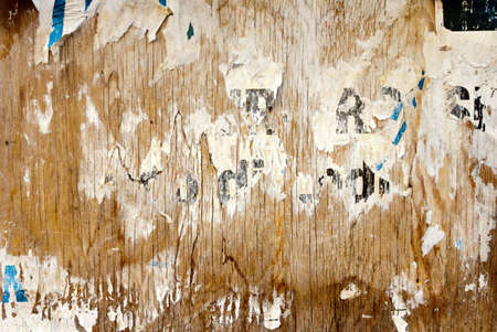 fragments of torn poster glued on wooden panel Stock Photo