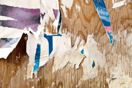 fragments of torn poster glued on wooden panel photo