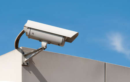 electronic survey: security camera against a clear blue sky Stock Photo