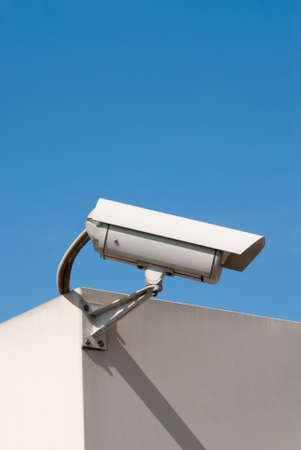 closed circuit television: security camera against a clear blue sky Stock Photo