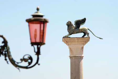 the winged lion symbol of the ancient republic of venice and a characteristic street lamp of St. Marks Square photo