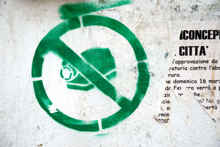 spray painting symbol against video surveillance upon white wall photo