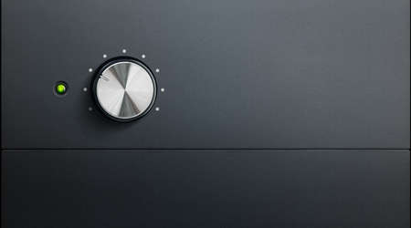 degrading black surface of amplifier with one knob and green warning led