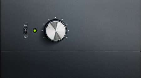 volume knob: degrading black surface of amplifier with one knob and power led Stock Photo