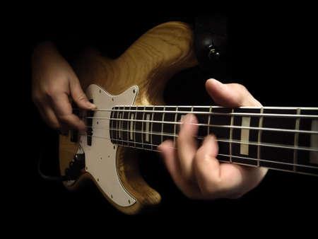 Bassist, spielt die Bassgitarre, die über schwarzem Hintergrund isoliert Lizenzfreie Bilder