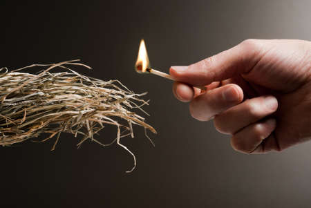 fire damage: male hand holding a match in the act of lighting a tuft of straw