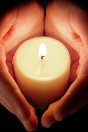 Hände, die zum Schutz der glühenden Flamme einer Kerze in der Dunkelheit Lizenzfreie Bilder