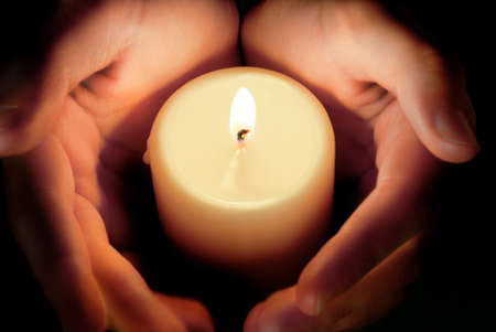 devout: hands protecting the glowing flame of a candle in the darkness Stock Photo
