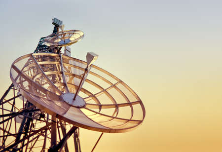 dishes on a telecommunications tower at the sunset Imagens