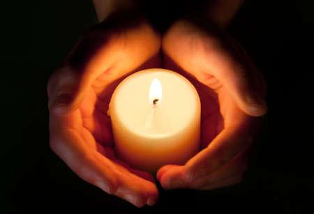kerze: H�nde, die sch�tzen der gl�henden Flamme einer Kerze in der Dunkelheit