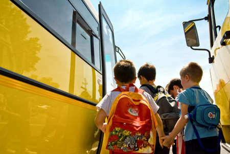 yellow schoolbus: children of primary school catching the schoolbus Editorial