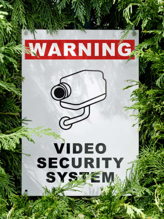 deter: video security system warning signboard on a fence hedge