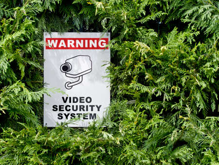 close circuit camera: video security system warning signboard on a fence hedge