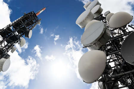 tv antenna: low angle view of two telecommunications towers against the sky Stock Photo