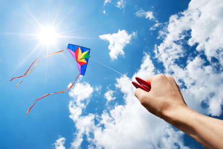 windy energy: kite flying in a beautiful sky with sun and clouds Stock Photo