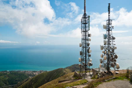 antenna: panorama with two telecommunications towers against sea and sky Stock Photo