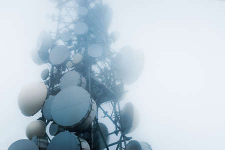 telecommunications tower into the clouds Stock Photo