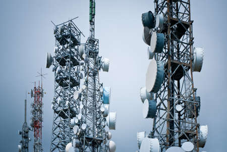 wireless: telecommunications towers against a gray sky