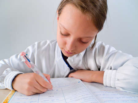 primary school girl doing homework over white background photo