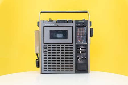Dirty old 1970s style cassette player radio on a yellow background.