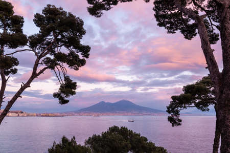 Naples, Italy. View through the trees from Posillipo of the beautiful city of Naples, with a wonderful sky with the colors of the sunset.