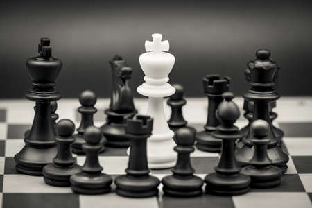 Concept of a person surrounded by enemies, threatened, with no way out. Made with chess figures on the chessboard.