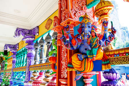 Representation of Hindu gods and tourists climbing a colorful stairs leading to the Batu Caves in the background. Kuala Lumpur, Malaysia
