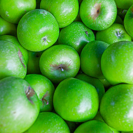 Fresh fruits vitamins background - bright green apples in market