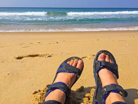 Legs in sandales on the seaside