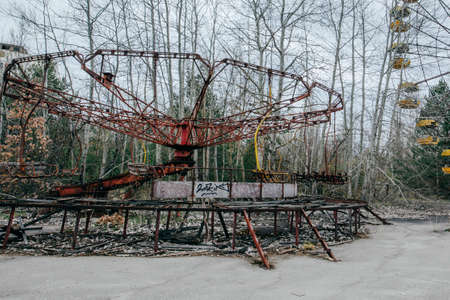 Abandoned carousel and abandoned ferris at an amusement park in the center of the city of Pripyat, the Chernobyl disaster, the exclusion zone, a ghost town