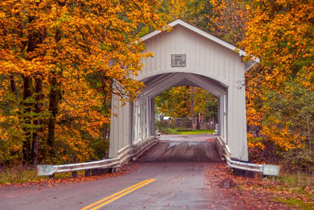 A white wooden covered bridge by golden autumn trees.