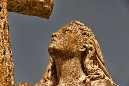 gazing: A statue of a woman gazing up at a cross.