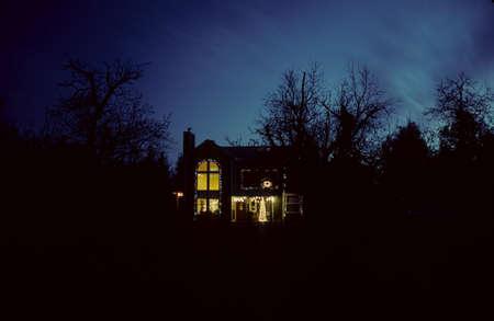 Kerstverlichting op een huis in het land 's nachts.