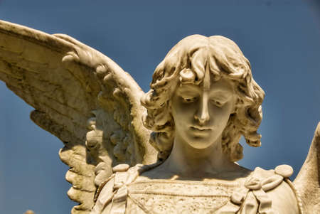 The head of a beautiful male stone angel statue.