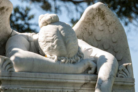 A stone angel with her head down on a tomb cries. Stock Photo