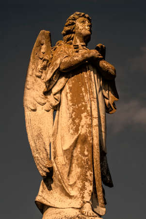 gazing: A statue of a male angel holding a cross, gazing up.