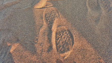 indentation: A Converse All Star shoe print in the sand.
