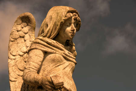 male angel: A stone statue of a male angel with wings, holding a cross. Stock Photo