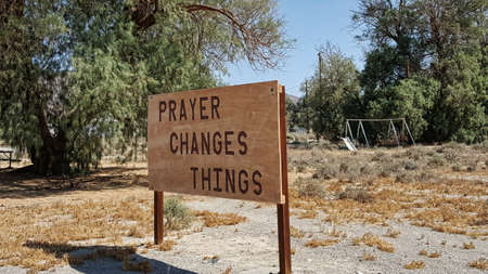 swing set: A sign saying Prayer Changes Things stands in front of a deserted sad swing set.