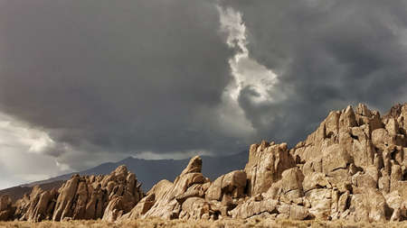 sierras: A patch of light in a stormy gray sky over big rock formations in the eastern sierras.