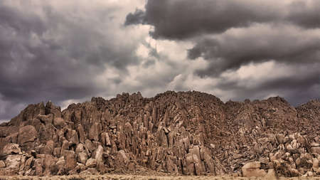 sierras: Storm clouds from over a big rock formation in a California desert valley in the eastern Sierras.