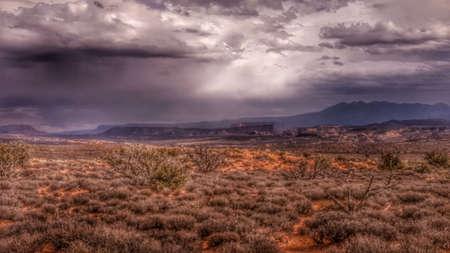 thunderhead: Light pours from rain clouds over a desert mesa.